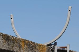 Кронштейн для спирального барьера на заборе из бетонных плит
