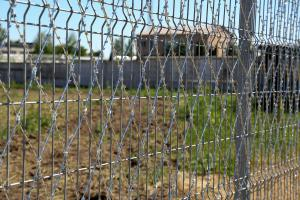 Welded grid fence and Piranha barbed mesh close-up