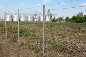 Забор из колючей проволоки на фоне поля