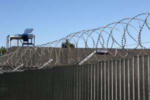 Барьер спиральный Кайман на заборе из профилированного листа