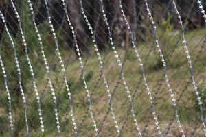 Колючая сетка Кайман на заборе из сетки рабица