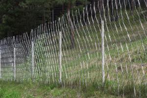 Старый забор, усиленный колючей сеткой Кайман