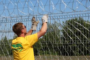 Installing Kayman barbed mesh on a fence of welded panels